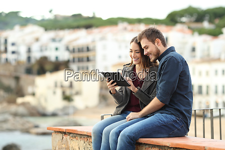 couple sitting on a ledge using