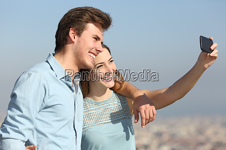 couple taking selfies in a city