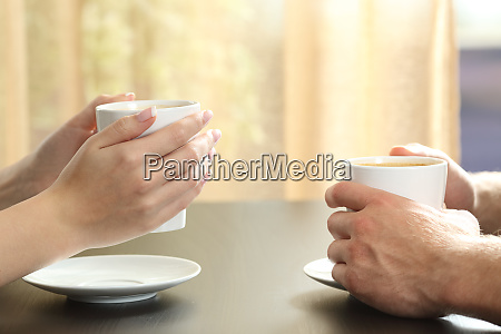 couple or friends hands holding coffee