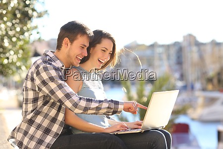 happy couple uses a laptop on