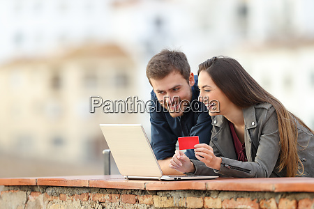 happy couple paying online with credit