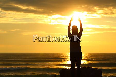 woman reaching sun at sunset on