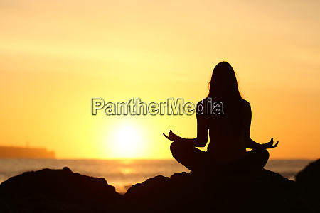 woman silhouette doing yoga at sunrise