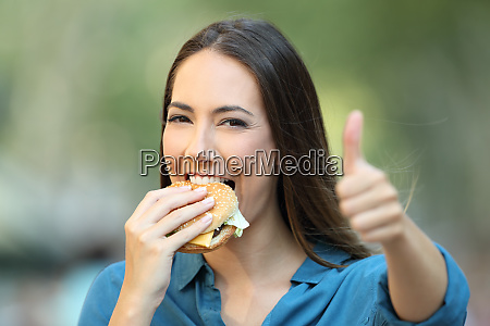 happy woman eats a burger with