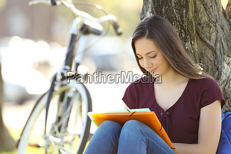 student learning memorizing notes outdoors