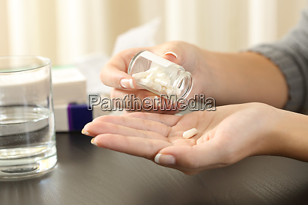 woman taking a pill from bottle