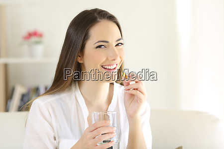 happy woman taking a vitamin supplement