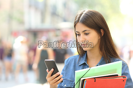 serious student checking smart phone in