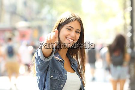 happy teen pointing at camera inviting