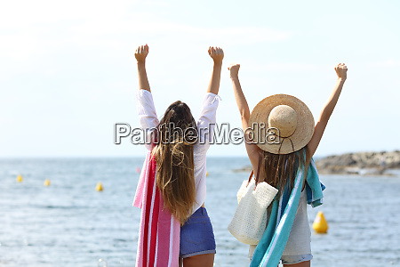 excited tourists raising arms celebrating vacation