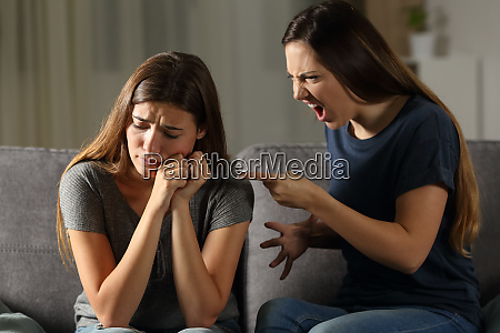 angry woman scolding her sad friend