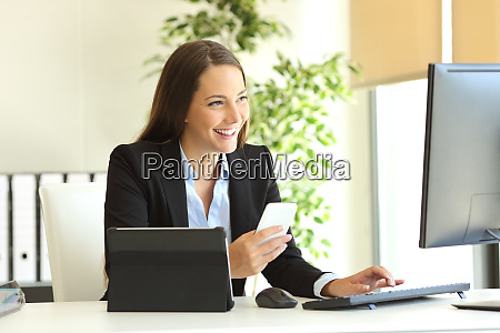 happy businesswoman working with multiple devices
