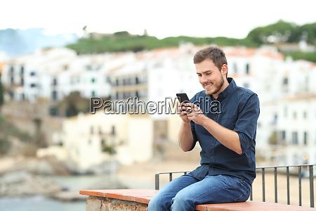 happy man texting on phone on