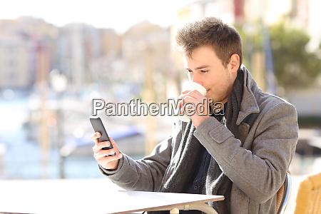 man drinking and cheking smart phone