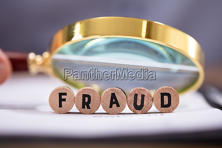 magnifying glass over the fraud word