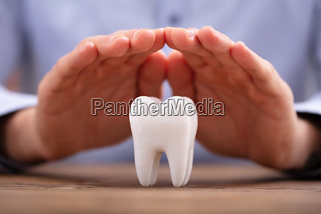 persons hand protecting white tooth