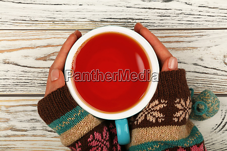 woman hands hold full cup of