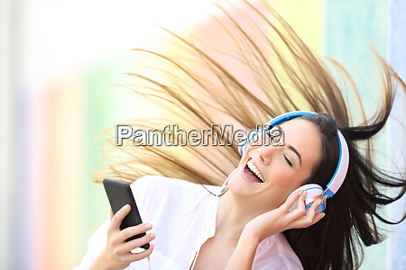 happy woman listening to music dancing