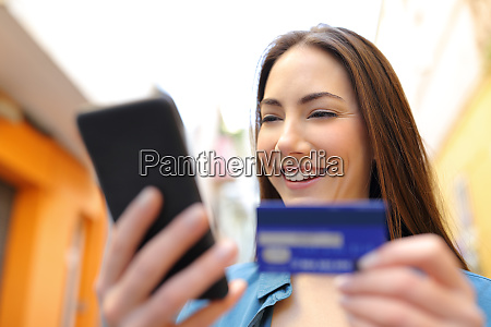 happy woman pays online with credit