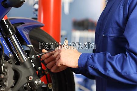 motorbike mechanic hands disassembling parts