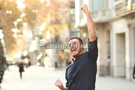 excited man raising arms celebrating sucess