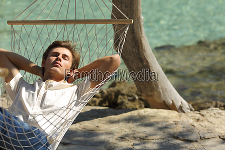relaxed man resting on a hammock