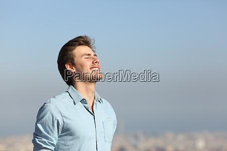happy man breathing deeply fresh air