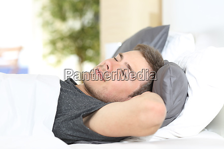 man sleeping on a comfortable bed