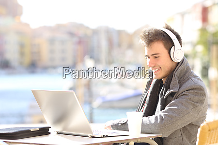 man with laptop and headphones working