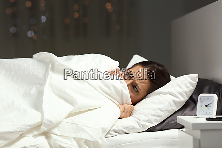 scared woman hiding under blanket on