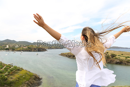 happy woman raising arms to the
