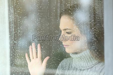 sad girl looking through a window