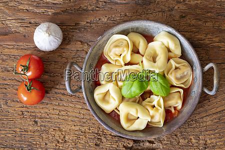 tortellini on wood with tomato sauce