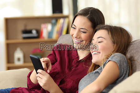 two happy roommates checking smart phone
