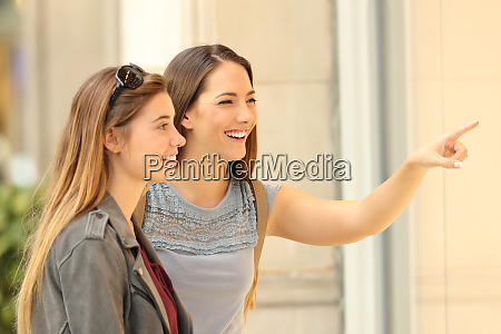 two happy shoppers watching a storefront