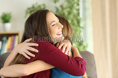 friends or sisters embracing at home