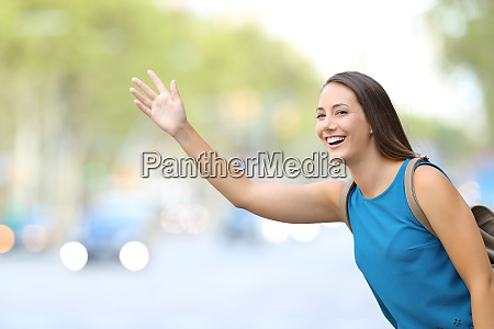 happy woman hailing taxi cab on