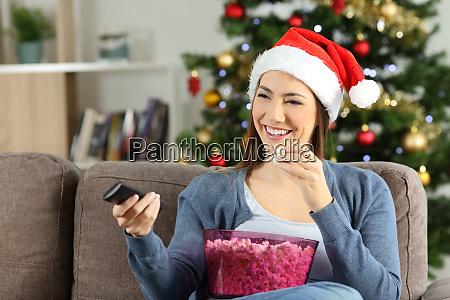 woman watching christmas tv porgram at