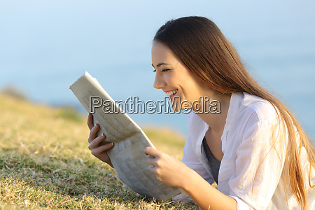 happy woman reading a newspaper lying