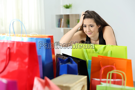 worried shopaholic woman after multiple purchases