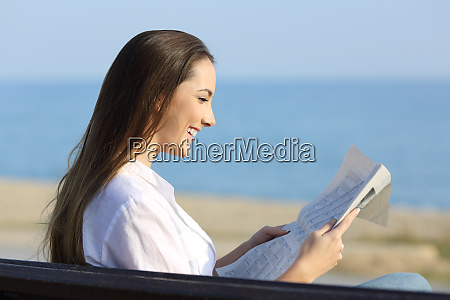 woman reading a newspaper sitting on