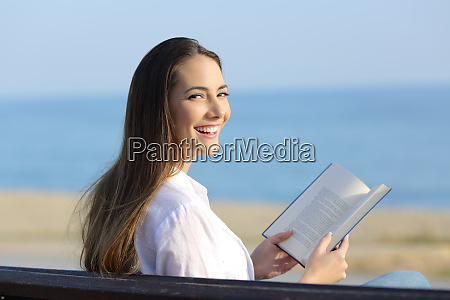 woman holding an open book looking