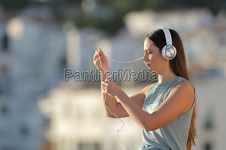 woman fighting with the headphones cord