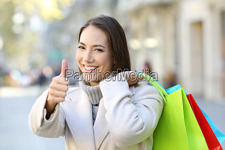 shopper with thumbs up holding shopping