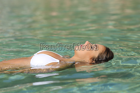 relaxed woman floating in a tropical