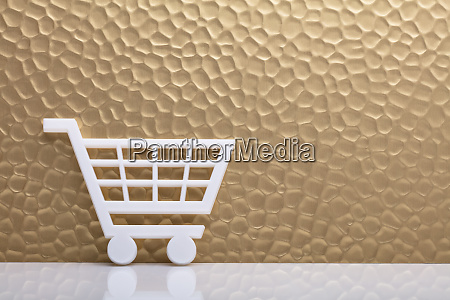 shopping cart leaning against textured wall