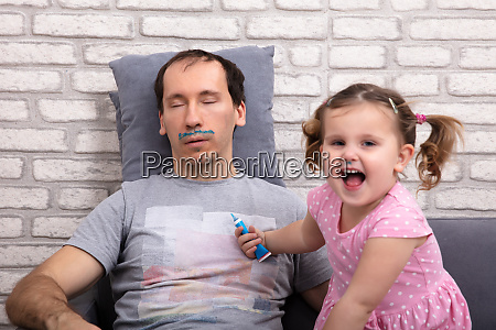 child painting fathers face while he