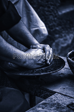 hands of a potter shaping clay