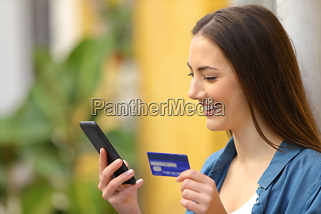 happy woman paying online using credit
