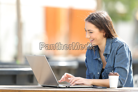 happy woman using a laptop sitting